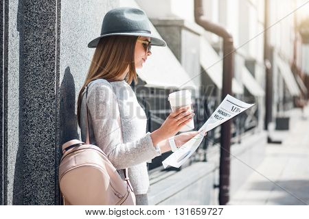 Interesting news.  Confident and glad modern young woman reading some articles in a newspaper and drinking coffee while being outside poster