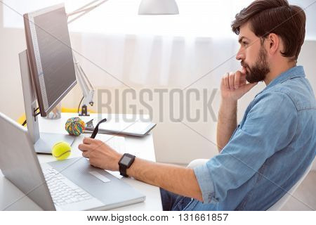 Real professional. Pensive young man looking at the screen of the computer and analyzing his work while holding glasses in his hand