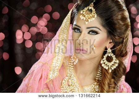 Portrait of a beautiful female model in classic indian asian bridal outfit looking sophisticated and classy with makeup and jewellery poster