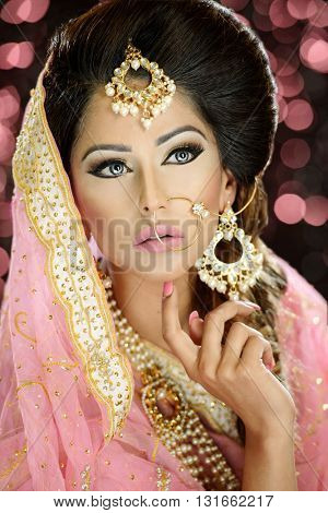 Portrait of a beautiful female model in classic indian asian bridal outfit looking sophisticated and classy with makeup and jewellery