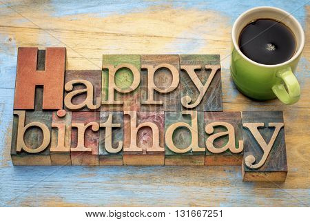 Happy Birthday greeting card - word abstract in vintage letterpress wood type stained by color inks with a green stoneware cup of coffee
