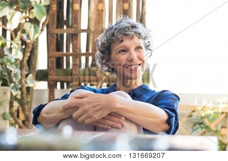 Senior woman relaxing in the house terrace. Happy smiling woman enjoying retirement. Cheerful mature woman thinking and looking up.