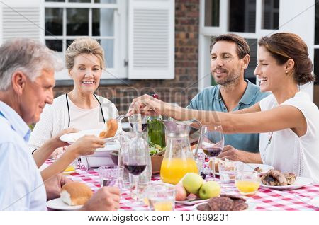 Happy family eating together outdoor. Cheerful woman serving bread to daughter. Smiling generation family sitting at dining table during lunch. Happy cheerful family enjoying meal together in garden.  poster