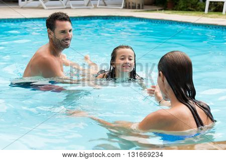 Parents teaching daughter how to swim. Little girl learning to swim with her mother and dad. Young family with daughter having fun in swimming pool.
