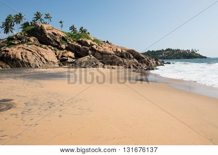 Rocks at the sandy beach of Kovalam in Thiruvananthapuram, Kerala. A part of a beach resort is also seen with green trees. On the background, the blue Arabian sea is seen.