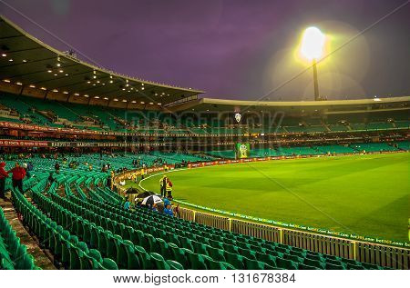 SCG SYDNEY NSW/AU JAN 26 2015 - India Vs South Africa Cricket rainwashed Match. Umpires trying desperately to have some game on pitch cover ready to be removedstill few people staying around in the stands. The sky turned amazingly purple.