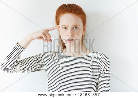 Headshot Of Angry And Mad Young Woman Gesturing With A Finger Against Her Temple: Are You Crazy? Ann
