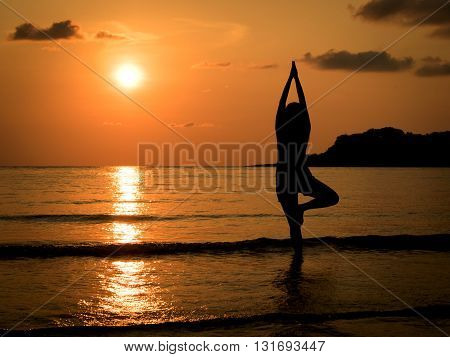 Silhouette of young woman practice yoga on sea beach at sunset in summer.