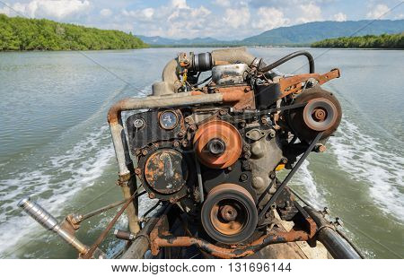 The engine of a long-tail boat with boat wake and tropical mangrove forest background in Phang Nga Bay National Park Thailand