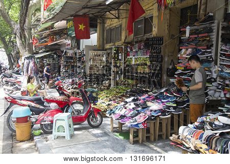 Hanoi, Vietnam - May 28, 2016: Vietnamese traders selling shoes and sandals at a flea market on the side walk of an old street in Hanoi capital.