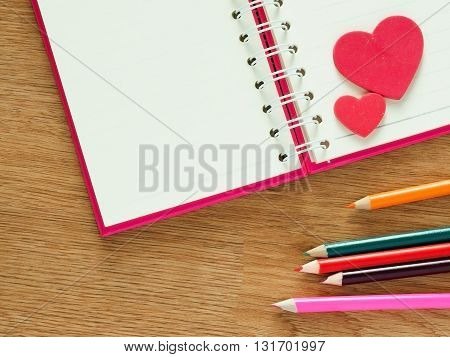 Valentines day background with red hearts book for diary and color pencils on wood floor. Love and Valentine concept.