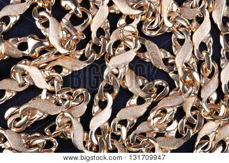 image of many yellow Gold Chain on black fabric