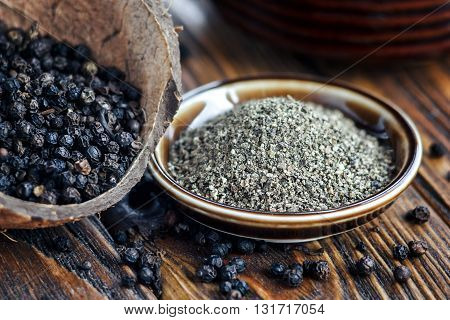 Whole and Ground black Peppercorns on old wooden table. Peppercorn Varieties. Milled black pepper. Black pepper corns and Black pepper Powder on wooden background. Close up, soft focus.