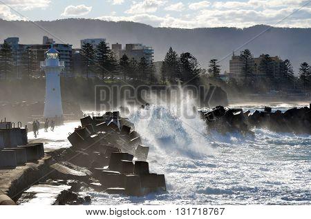 Big waves breaking over Wollongong harbor break wall near the lighthouse, Australia