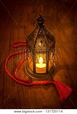 Ramadan lamp with an Islamic prayer beads on wooden background.