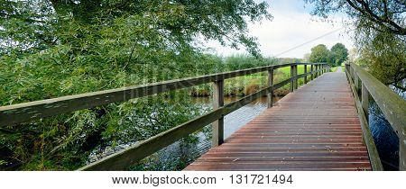 Wooden footbridge over a narrow river in a rural landscape. It is autumn and the first yellowed leaves fall from the willow trees already.