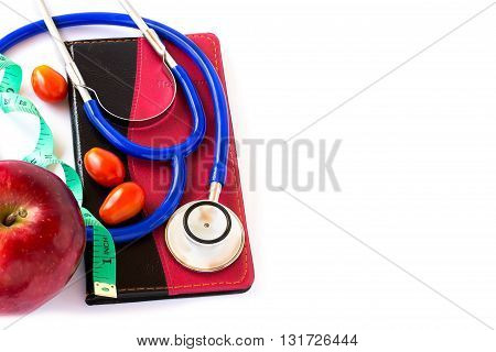 Bule stethoscope and red apple measuring tape on notebook on a white background