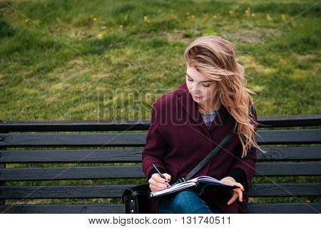 Thoughtful attractive young woman sitting on bench and writing in notebook outdoors