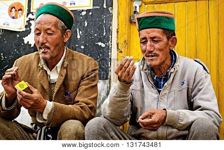 Sangla, India- May 01, 2016: Indian men of Himachal Pradesh state of India in traditional Kinnaur hats in Himalayas lighting cigaretts