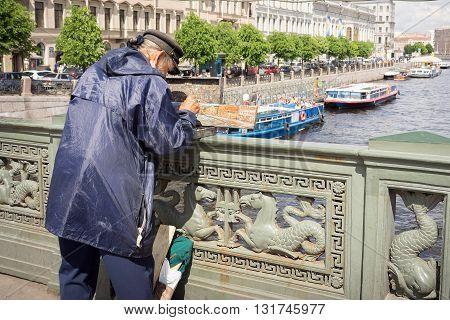 St Petersburg Russia - May 26 2016: Unidentified painter paints on Nevskom prospectus the boats in Fontanka river on Anichkov bridge. Saint-Petersburg has also been nicknamed