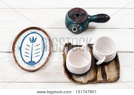 Old clay tea set for two people on white wooden background. Close-up of teapot, two cups and plate. Rustic clay utensil for tea with dry flower