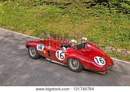 PASSO DELLA FUTA (FI) ITALY - MAY 21: driver and co-driver on a vintage competition car Ferrari 750 Monza Spider Scaglietti (1954) travel in Tuscany during the classic car race Mille Miglia on May 21, 2016 in Passo della Futa (FI) Italy