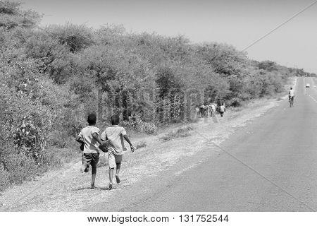 Boys Running Along A Road In Tanzania