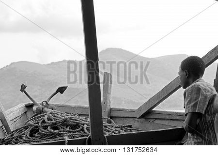 KIGOMA TANZANIA - JUNE 13: young boy on a ship on Lake Tanganyika looks overboard on June 13 2013 in Kigoma. Fishing is the main livelihood of the communities that live near the sea and the lakes