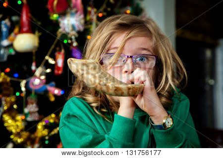 A young Christian girl blows a Jewish Shofar on Christmas morning. This illustrates a melding of two religions culture and tradition.