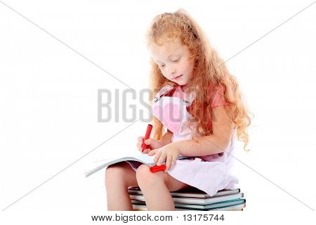 Portrait of a little girl sitting on a stack of books. Isolated over white background.
