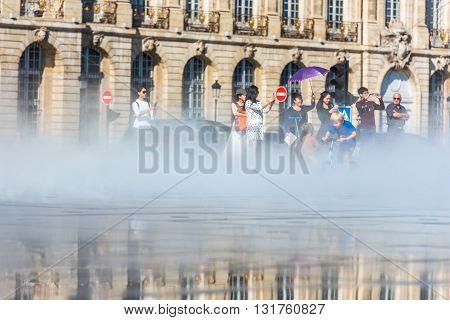 People Having Fun In A Mirror Fountain In Bordeaux, France