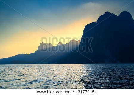Beautiful sunset and sunbeam between mountain sunray at mountain and sea or lake Golden sunray at Suratthani Thailand. Sunray at evening.