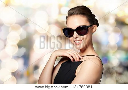 accessories, eyewear, fashion, people and luxury concept - beautiful young woman in elegant black sunglasses over holidays lights background