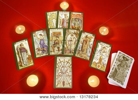 Tarot Cards With Candles On Red Textile