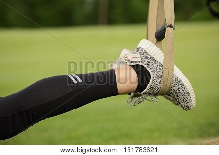 Closeup of man's legs while training before or after jogging long distance. Man's legs in jogging shoes in green park or forest.