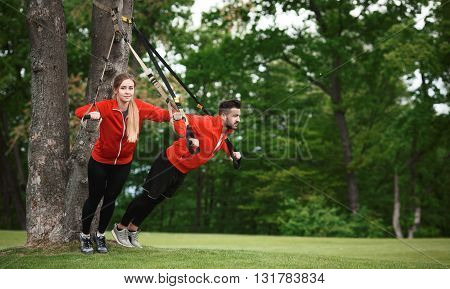 Fitness man and woman training in green park with suspension trainer sling. Beautiful couple in red jackets preparing for jogging: stretching, exercising, etc.