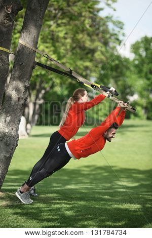 Couple training with suspension trainer sling in green park near spring or summer tree. Man and woman in red jackets preparing for sports competitions.