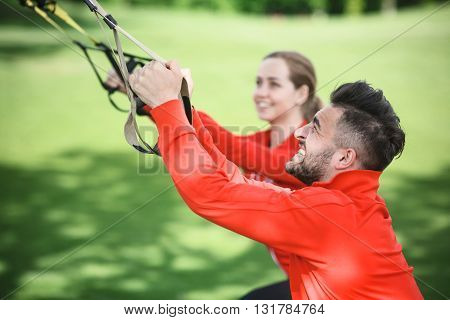 Closeup portrait of sport and fitness man training in park with his partner or girlfriend. Beautiful couple using suspension trainer.