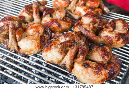 close up of fresh barbecue chicken on open grill