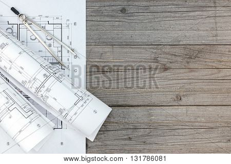 Rolls Of Architectural Blueprints With Drawing Compass On Gray Wooden Desk