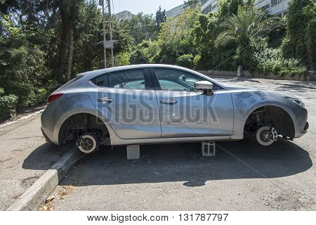 Haifa, Israel, April 4, 2016 : Car on blocks with four stolen wheels in the street