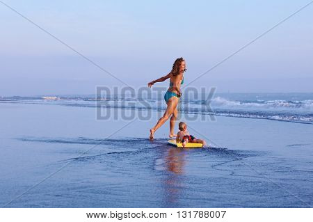 Happy family having fun - mother with baby son on surfing board run by water pool along sea surf of sunset beach. Active parent and kid lifestyle people activity on summer beach holiday with children