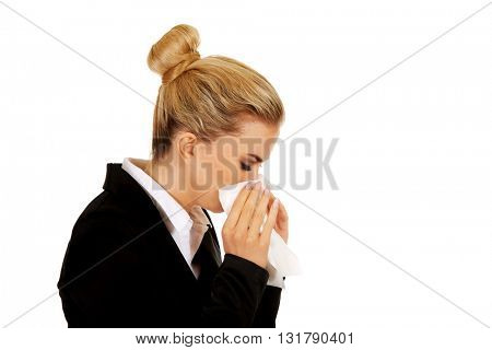 Businesswoman with an allergy sneezing into tissue