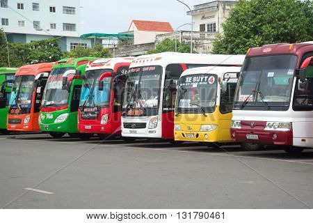 VUNG TAU, VIETNAM - DECEMBER 23, 2015: Multi-colored long-distance buses are on the landing of passengers at the bus station of the city of Vung Tau