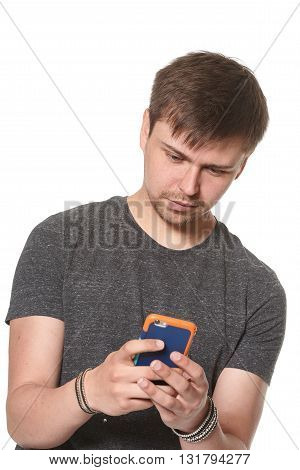 Casual young man texting on mobile phone isolated on white
