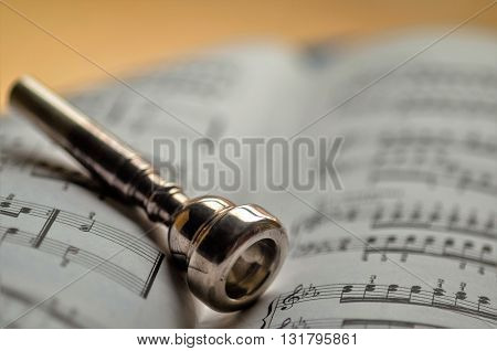 trumpet mouthpiece posed on a book of music
