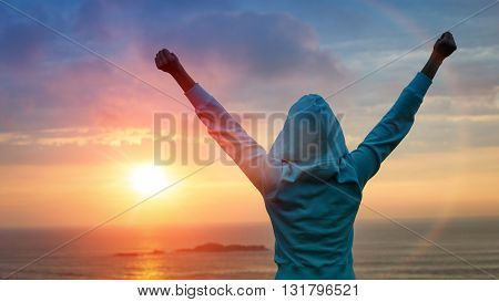 Sport and life achievements and success concept. Rear view sporty girl raising arms towards beautiful glowing sunshine.