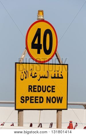 road sign Reduce Speed now in English and Arabic