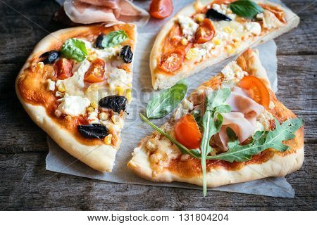 Photos of mini pizzas slices on rustic background