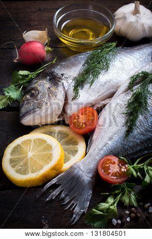Photos of raw dorada fish on rustic background